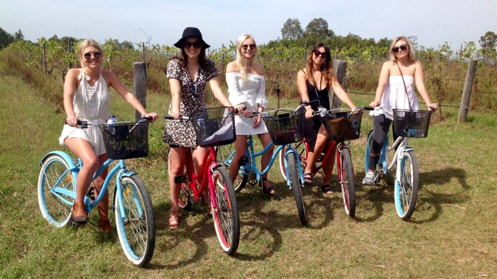 girls riding bicycles though the vineyards